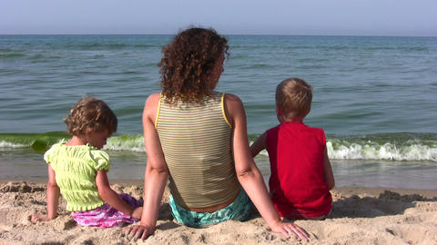 behind mother with children sit on beach Footage