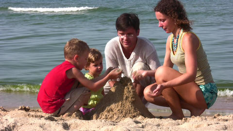 family of four play with sand Stock Video Footage