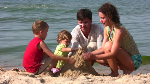 family of four play with sand Footage