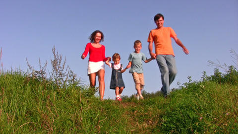 family of four walking on meadow Stock Video Footage