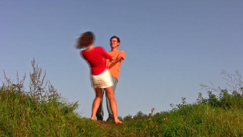 couple whirl on meadow Stock Video Footage