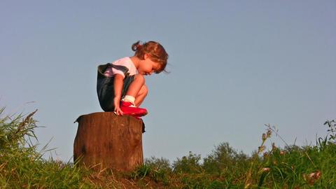 little girl climb on stump Stock Video Footage