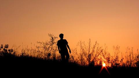 walking man silhouette on sunset sky alone Stock Video Footage