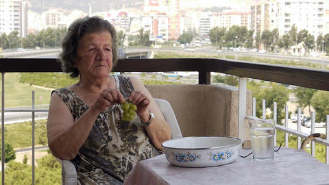 Old retired woman eating grapes on balcony Stock Video Footage