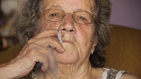 Old retired woman smoking cigarette Footage