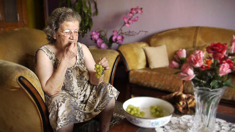 Old retired woman eating grapes Footage
