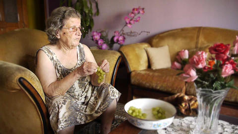 Old retired woman eating grapes Stock Video Footage