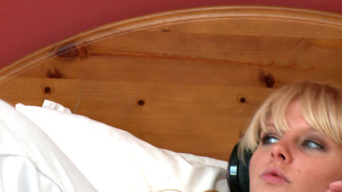 Pensive woman lying on bed listening music Footage