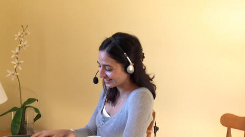 Jolly woman talking on internet with headset on Footage