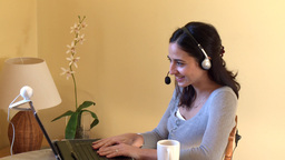 Jolly woman talking on internet with headset on Stock Video Footage