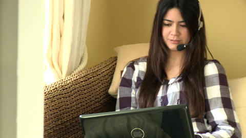 Happy woman working at a laptop with headset Footage