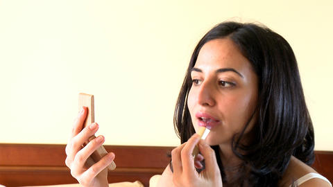Portrait of a voluptuous woman putting lipstick Stock Video Footage