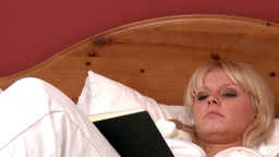 Delightful woman lying on bed reading a book Stock Video Footage