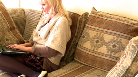 Peaceful woman sitting on sofa using a laptop Footage