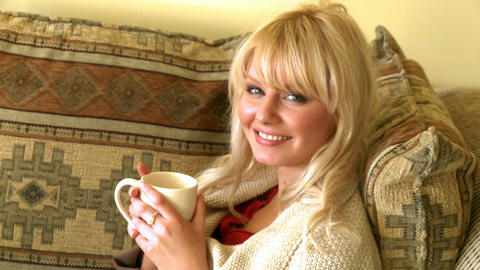 Portrait of a blond woman drinking coffee sitting Stock Video Footage