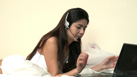 Animated woman lying down on bed using a headset Stock Video Footage