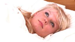 Halfawake woman lying in bed Stock Video Footage