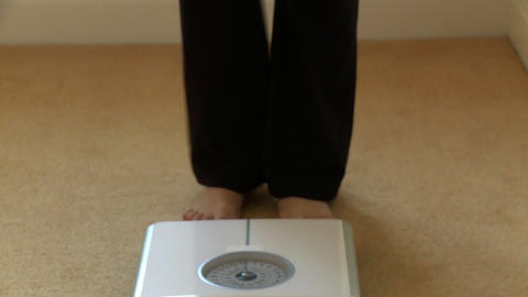 Close up of a woman checking her weight Footage