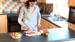 Pretty woman cutting vegetables Footage