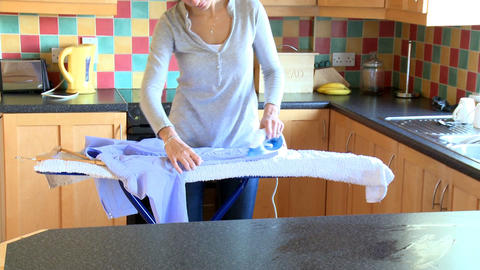 Brunette woman ironing a shirt Footage