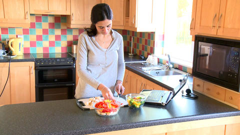 Beautiful woman preparing a salad and looking at a Footage
