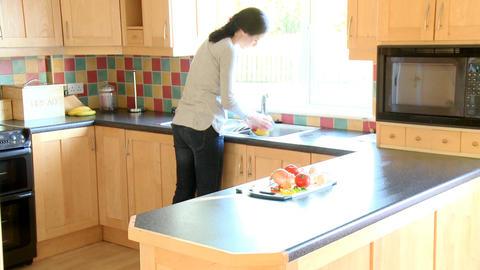 Brunette woman rinsing vegetables Stock Video Footage