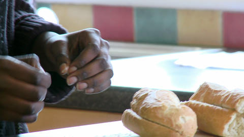 Close up of AfroAmerican woman cutting bread Live Action