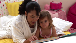 Pretty woman reading a book with her daughter Footage