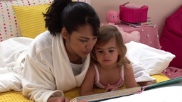 Pretty woman reading a book with her daughter Stock Video Footage