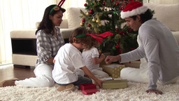 Happy family discovering the gifts on Christmas da Footage