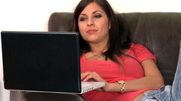 Charming woman using a laptop sitting on sofa Footage