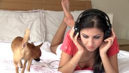 Elegant woman lying down on bed listening music Footage