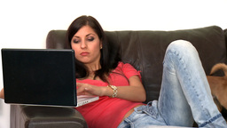 Radiant woman using a laptop sitting on sofa Footage
