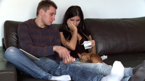 Upset couple doing their accounts sitting on sofa Stock Video Footage