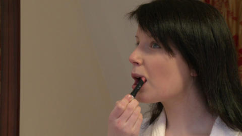 Young woman putting lipstick Stock Video Footage