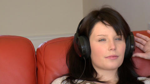 Attractive woman listening music sitting on bed Footage