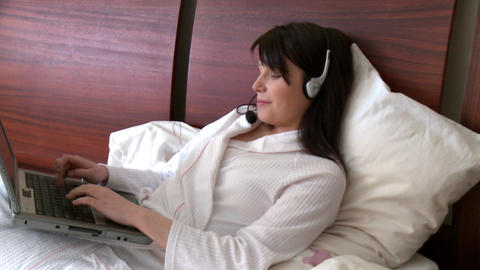Smiling woman using a laptop with headset on Footage