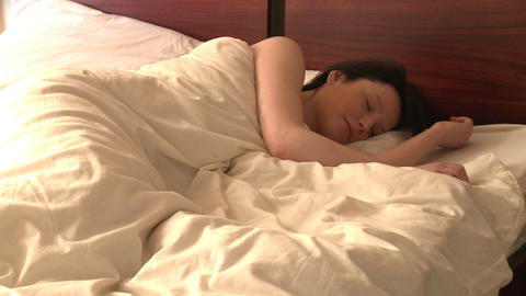 Snoozing woman looking at alarm clock Stock Video Footage