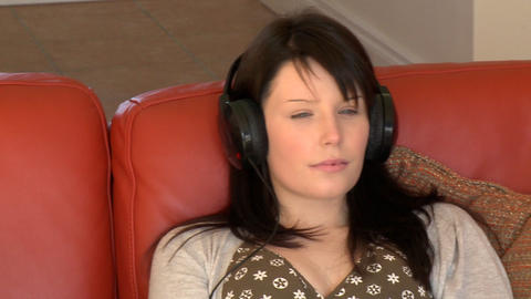 Relaxed woman sitting on sofa and listening music Footage