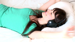 Delighted woman listening music lying on her bed Footage