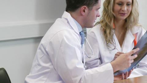 Two young doctors looking at an xray in a hospital Stock Video Footage