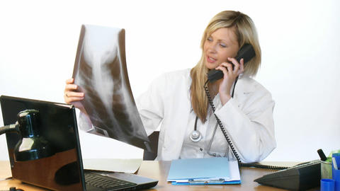 Female doctor on phone and studying an xray Footage
