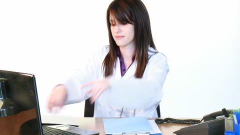 Brunette doctor on phone and using a laptop in off Footage