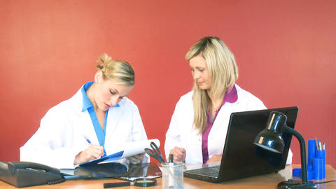 Female doctors signing documents in office Stock Video Footage