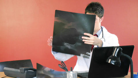 Male doctor using a laptop and studying an xray fo Footage