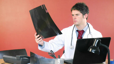 Male doctor using a laptop and studying an xray fo Stock Video Footage