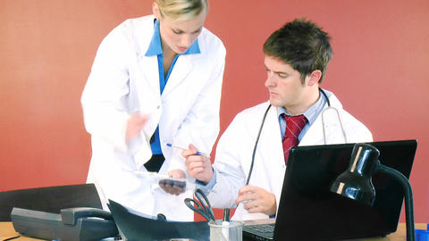 Male and female doctors signing documents in offic Footage