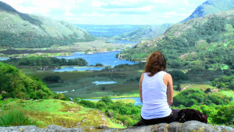 Young woman sitting on top of a mountain Footage