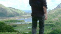 Young man sitting on the top of a mountain Stock Video Footage