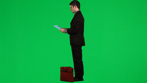 Businessman reading a report against green screen footage Footage
